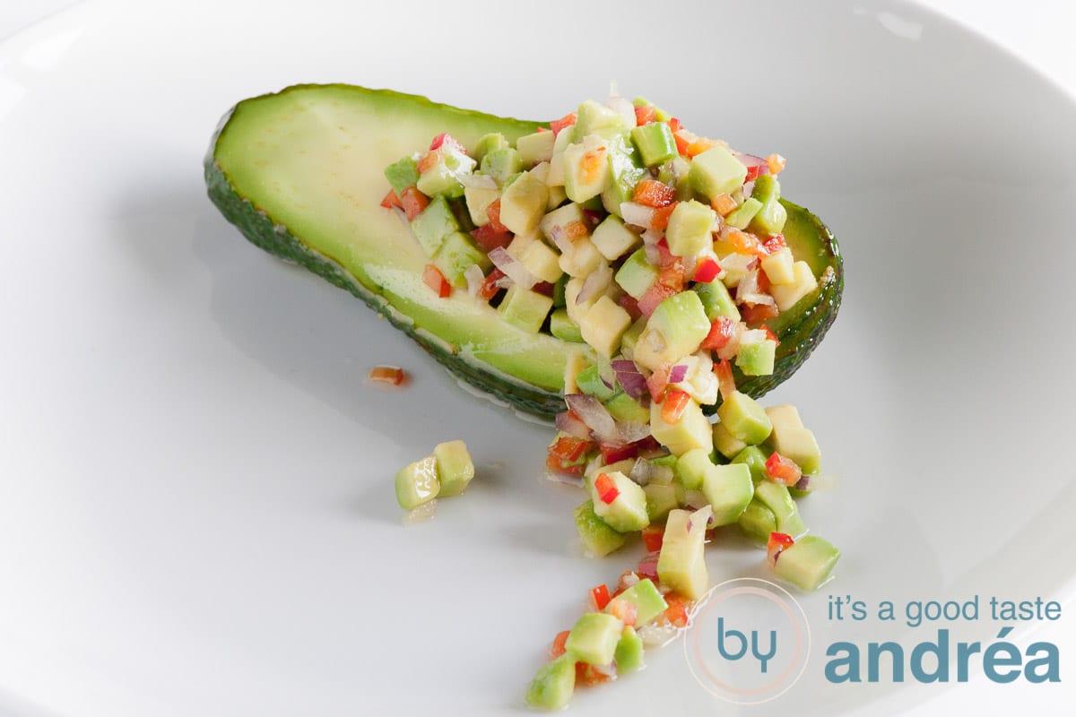 Een avocado met allerlei heerlijke groenten die naar beneden verspreiden