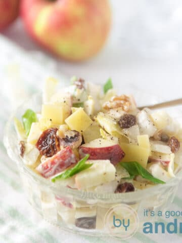 a square photo with a bowl of brussels endive salad with raisins etc