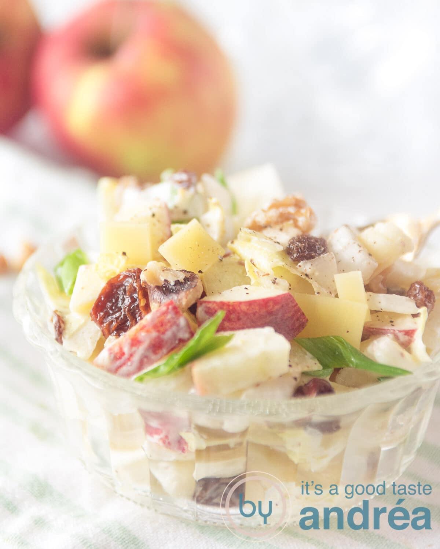 Driekwart glazen kommetje gevuld met een salade van witlof, appel en rozijnen