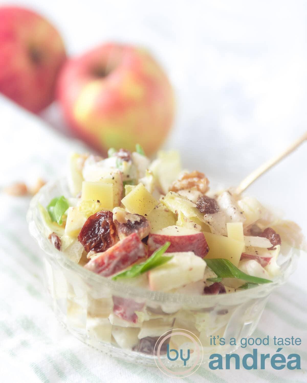 Een schaaltje gevuld met witlofsalade met appel, walnoten, rozijnen. Appels in de achtergrond