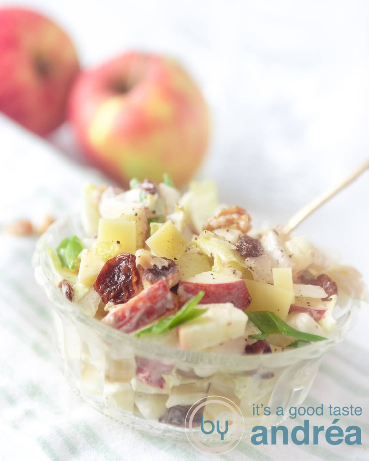 a bowl with chicory salad with apple in the front. Some apples in the back