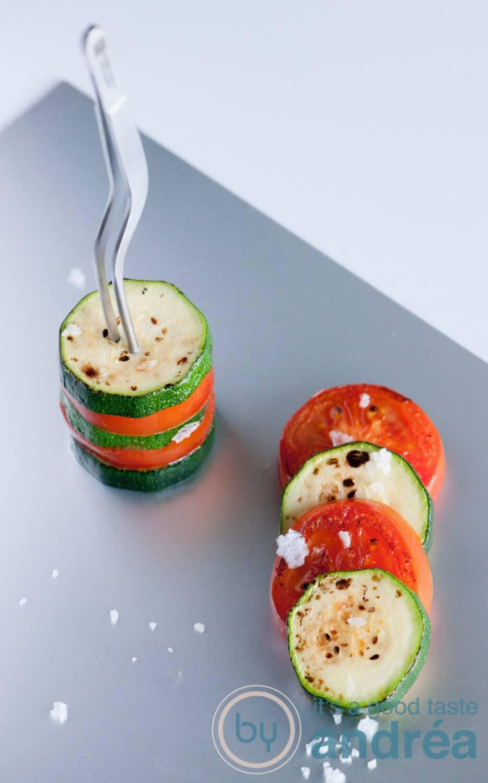 Een aluminium plaat met geroosterde courgette en tomaat met een pincet bij elkaar gehouden