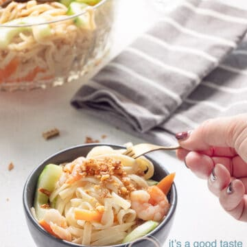 a hand taking a bit of the noodle salad in a great bowl. A big bowl filled with salad and a grey towel are in the back