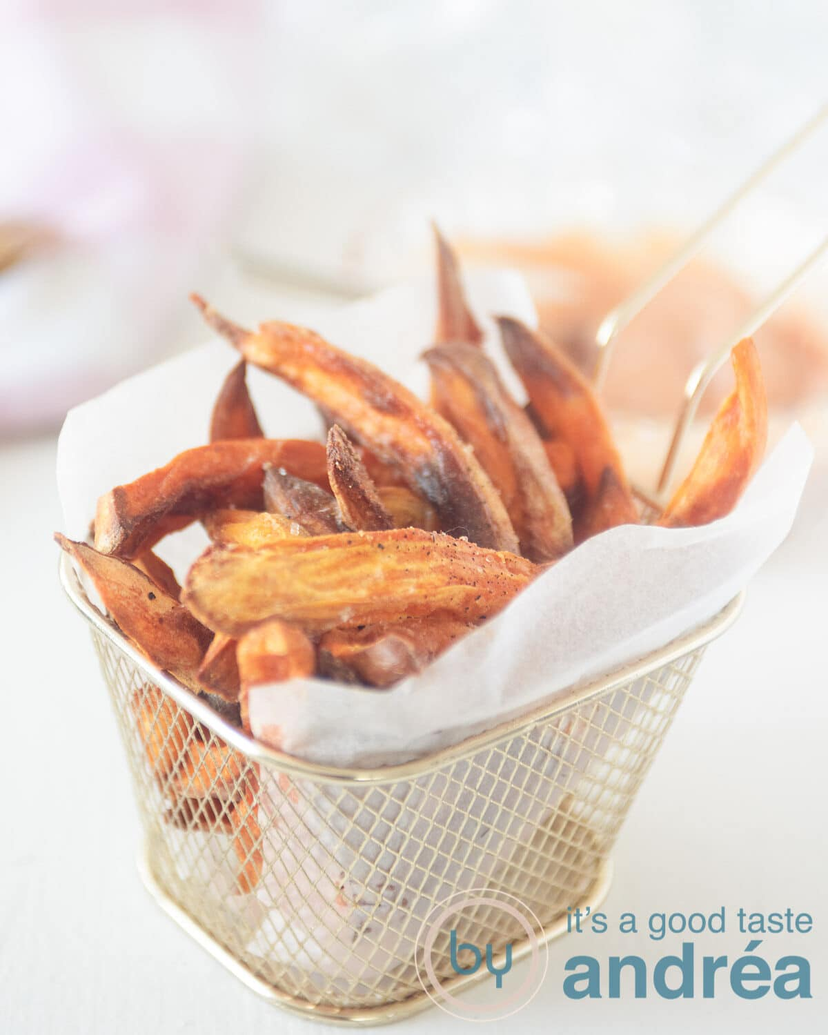 In the middle a golden fries tray in which a baking paper is folded with sweet potato fries in it