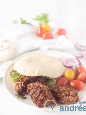 A white plate with a pita bread filled with cevapi, lettuce and tomatoes. What vegetables are around the plate