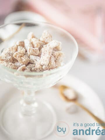 A glass bowl filled with fresh ginger candies. A cup of coffee in the background