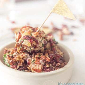 A white dish with goat cheese balls. A golden flag sticks in it