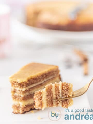 A fork holding a bite of gingerbread. In the background a slice of cake and the whole thousand layers cake