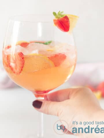 A hand holding a glass of strawberry gin cocktail with a strawberry and lemon garnish